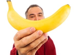 Man holds a banana in front of his face